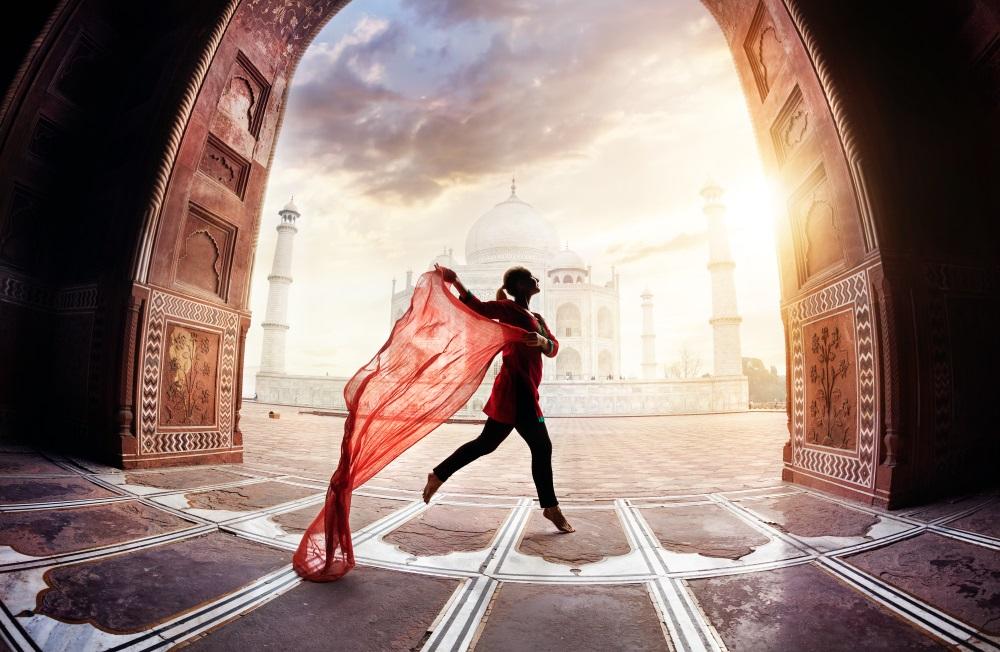 Indie Woman with red scarf dancing near Taj Mahal in Agra, Uttar Pradesh, India